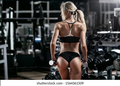 beautiful woman bodybuilder in dark GYM with dumbbell turn back, fitness concept, horizontal photo