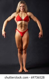 A beautiful woman bodybuilder posing in red bikini