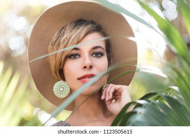 Beautiful Woman in a Boho Style Hat Behind Leaves from a Plant
