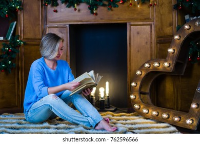 beautiful woman with book on the background of a christmas interior