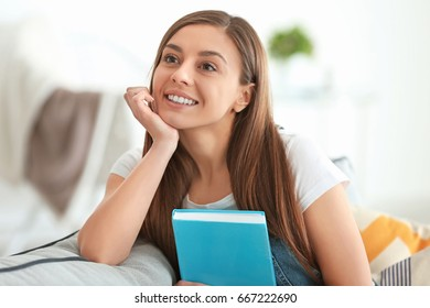 Beautiful woman with book sitting on couch