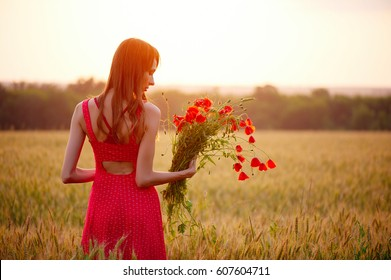 beautiful woman with bouquet of poppies in wheat field at sunset, warm the