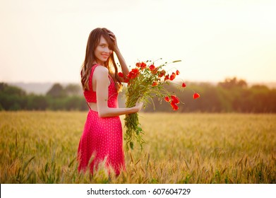 beautiful woman with bouquet of poppies in wheat field at sunset
