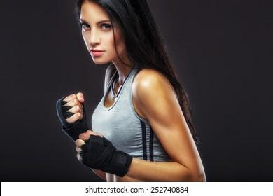 beautiful woman boxer portrait over dark background