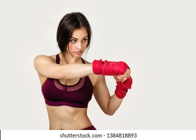 beautiful woman boxer with red boxing tape on wrist. Fitness girl preparing for boxing training