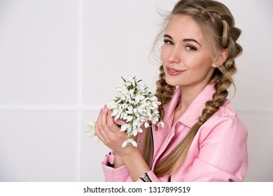 Beautiful woman with braided hair in a pink leather jacket with a bouquet of snowdrops. It's spring.