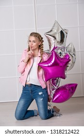 Beautiful woman with braided hair in a pink leather jacket with ballons. It's spring.