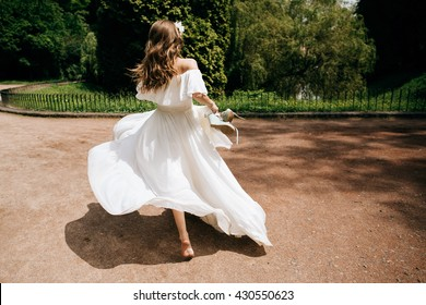 beautiful woman bride running barefoot in white dress in summer park