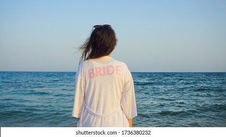 Beautiful woman or bride standing on the sand of beach and watching sea during the honeymoon after wedding. Pretty female on beach looking at ocean and horizon. Wavy haired alone girl on honeymoon.