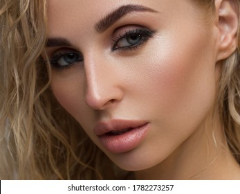 Beautiful woman with bright make up eye with sexy black liner makeup. Fashion big arrow shape on woman's eyelid. Natural lips. Chic evening make-up. Blonde long wave hair. Shining face skin