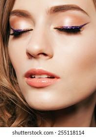 Beautiful woman with bright make up eye with sexy violet liner makeup. Fashion glitter arrow shape on woman's eyelid. Chic evening make-up