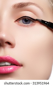 Beautiful woman with bright make up eye with sexy black liner makeup. Fashion arrow shape. Chic evening make-up