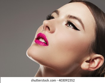 Beautiful woman with bright make up eye with sexy black liner makeup. Fashion big arrow shape on woman's eyelid. Chic evening make-up
