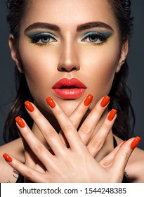 Beautiful woman with bright red lipstick and  nails. Gorgeous girl with blue eye makeup. Portrait of an attractive girl with orange nails on her face. Fashion  model. Sexy face of a pretty lady.