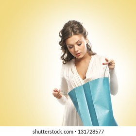 Beautiful woman with the bright shopping bags over the yellow background