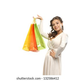 Beautiful woman with the bright shopping bags isolated on white