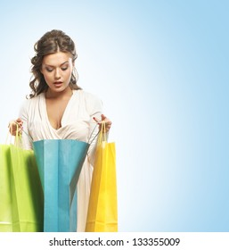 Beautiful woman with the bright shopping bags over the blue background