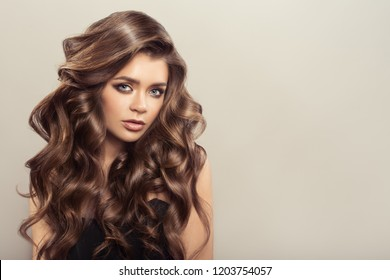 Beautiful woman with brown curly hair. Hairstyle.