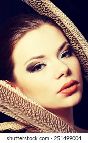 Beautiful woman with brown professional make-up with feathers