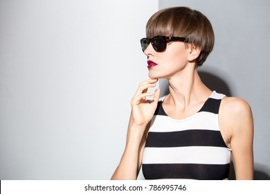 Beautiful woman with brown short hair wearing stripes dress over white and grey background. Haircut. Hairstyle. Fringe. Professional makeup