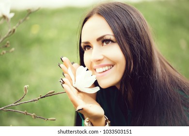 beautiful woman with brunette hair and smiling face smelling spring magnolia flower white color on green background