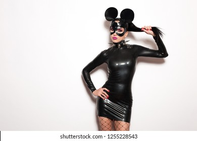 Beautiful woman brunette model vamp mistress dominatrix bdsm woman in glamour latex dress and black leather fetish mouse mask posing in sex shop white room