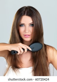 Beautiful woman is  brushing her long hair