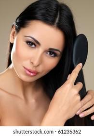 Beautiful woman is  brushing her long hair