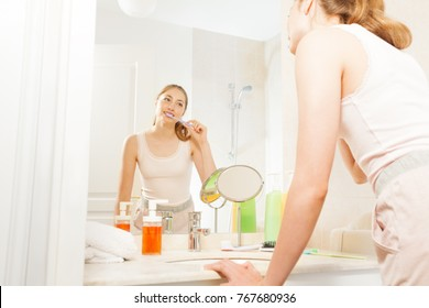 Beautiful woman brushing her teeth in the bathroom