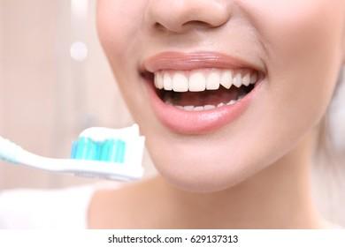 Beautiful woman brushing teeth, closeup