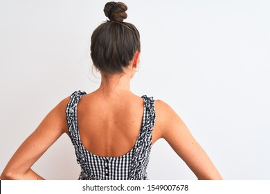 Beautiful woman with bun wearing casual dress standing over isolated white background standing backwards looking away with arms on body