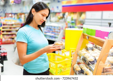 Beautiful woman buys bakery products