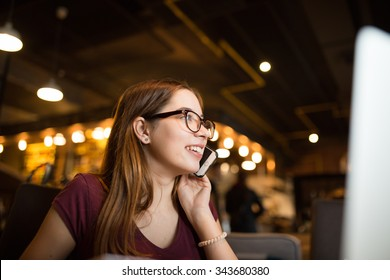 Beautiful woman in a cafe talking on the phone and smile