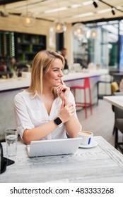 Beautiful woman at a cafe, wearing smartwatch.