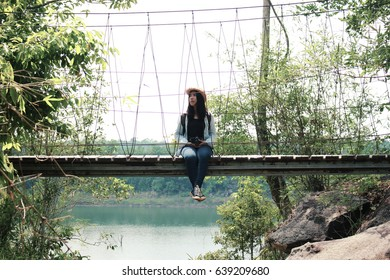 Beautiful woman and camera with backpack in the jungle on the mountain. concept travel, color of vintage tone and soft focus.