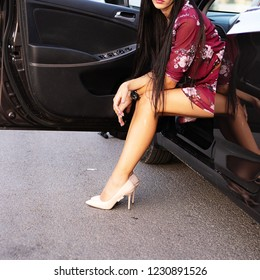 beautiful woman in the car outdoor . Young rich slim girl driver . Lady with long healthy  hair. Young woman with slim legs in high heels getting out of car