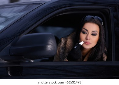 Beautiful woman in car in snowy winter outdoors