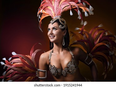 Beautiful woman in a carnival costume with rhinestones and feathers. Attractive female cabaret dancer in sexy costume with red and pink feathers.
