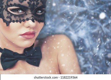 Beautiful woman with carnival mask looking at camera, christmas night. Cristmas party. Secret. Fashion. Venetian carnival. Hot babe.