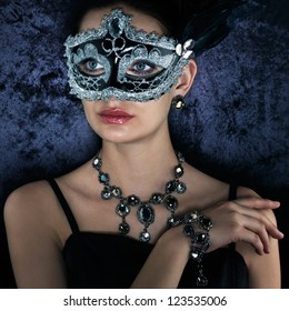Beautiful woman in carnival mask on dark velvet background