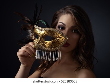 Beautiful woman with carnival mask on a black background