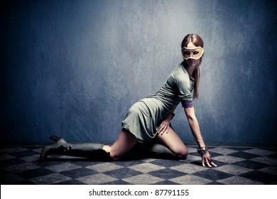 beautiful woman with carnival mask posing on floor,  full body shot, indoor shot