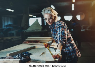 Beautiful woman carpenter designer works with ruler, make notches on the tree in workshop.  Image of modern femininity. Concept of professionally motivated women