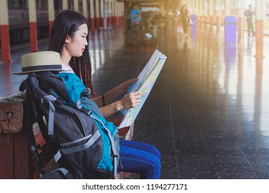 Beautiful woman carrying a backpack carrying a map of a railway station.