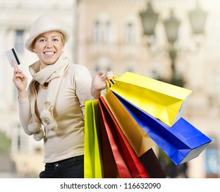 Beautiful woman carrying a lot of colorful shopping bags down town