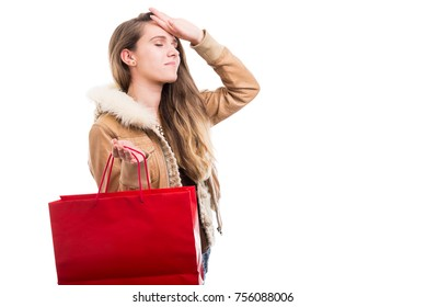 Beautiful woman carrying paper bag and looking tired after doing shopping all day
