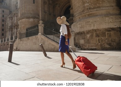 Beautiful woman carrying suitcase while walking down the street