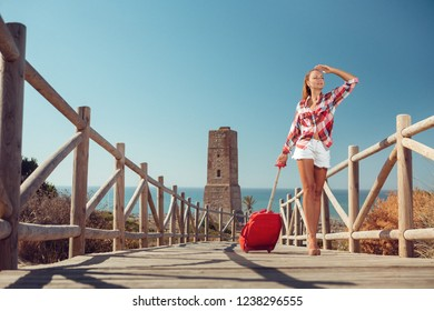 Beautiful woman carrying suitcase while walking up on bridge