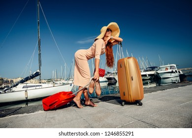 Beautiful woman carrying suitcase while walking down the Yacht club