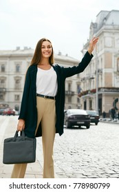 Beautiful Woman Catching Taxi Car On Street. Portrait Of Smiling Business Woman On Way To Work Stopping Taxi Car Outdoors. Business Style. High Quality Image.